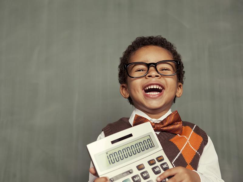 Jeune garçon éclatant de rire et tenant une calculatrice.