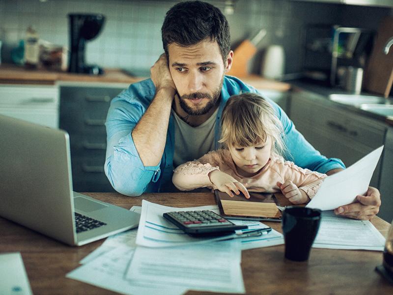 Un père semblant soucieux, tenant dans ses bras un jeune enfant, devant un ordinateur portable et une calculatrice.