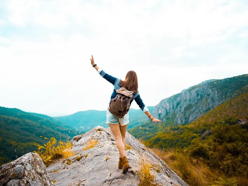 Jeune adulte au sommet d'une montagne
