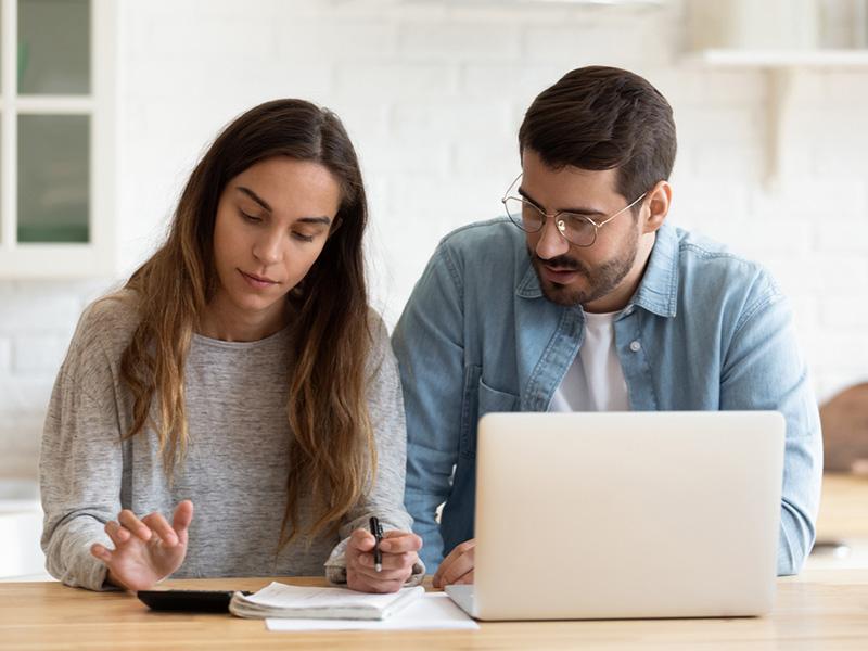 Jeune couple travaillant à l'ordinateur.