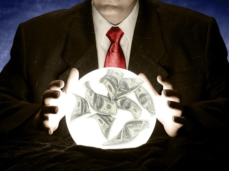 Des mains posées sur une boule de crystal renfermant des dollars