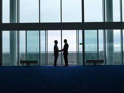 Deux personnes se serrent la main lors d'un départ.