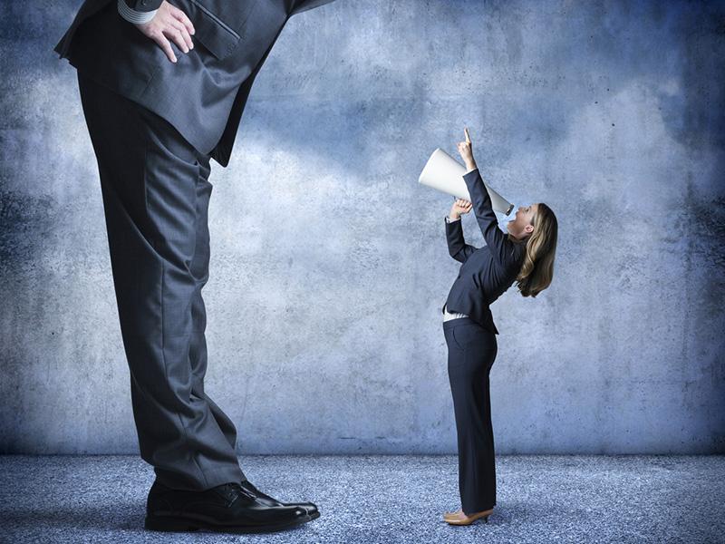 Une femme, minuscule, criant dans un porte-voix à un homme, géant.