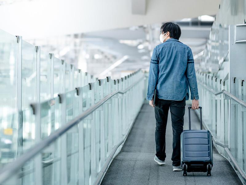Voyageur portant un masque et tirant sa valise dans un aéroport désert.