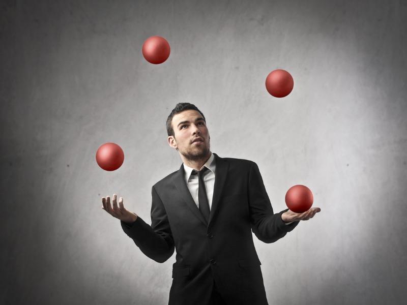 Un homme d'affaires qui jongle avec 4 balles.