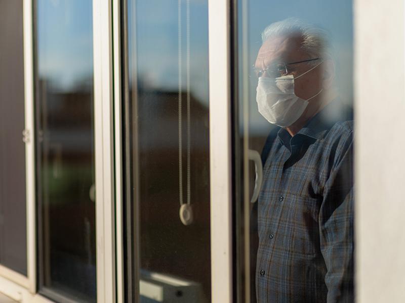 Homme âgé regardant par une fenêtre et portant un masque