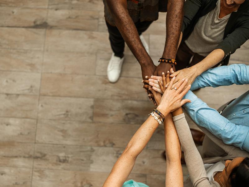 Des personnes de différentes origines ethniques joignent leurs mains.