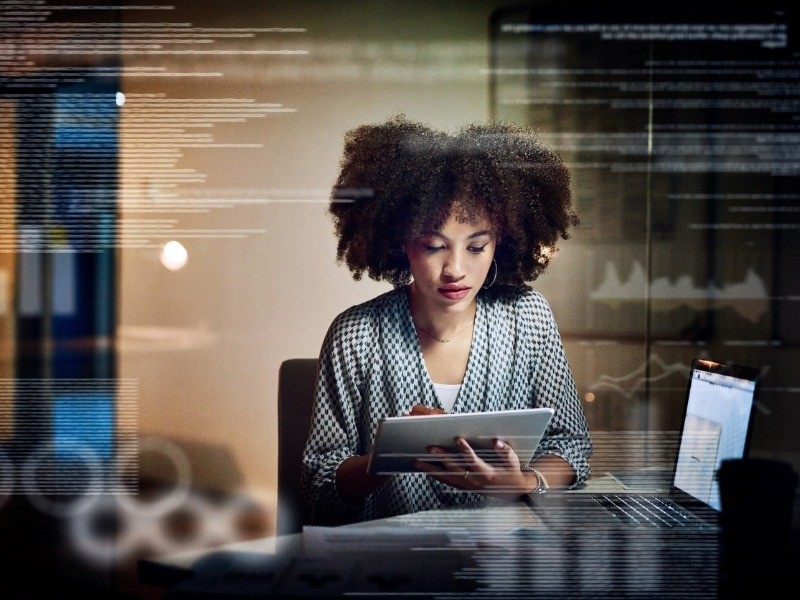 Une femme devant un ordi qui regarde sa tablette.