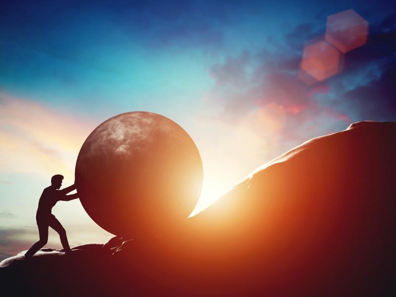 Un homme d'affaires pousse un rocher rond en haut d'une montagne alors que le soleil se couche.