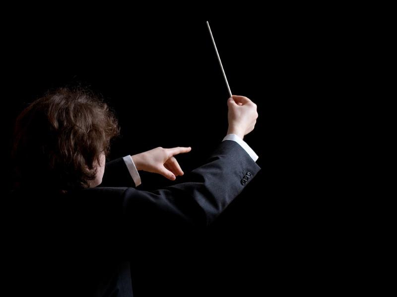 On voit un chef d'orchestre sur un fonds noir.