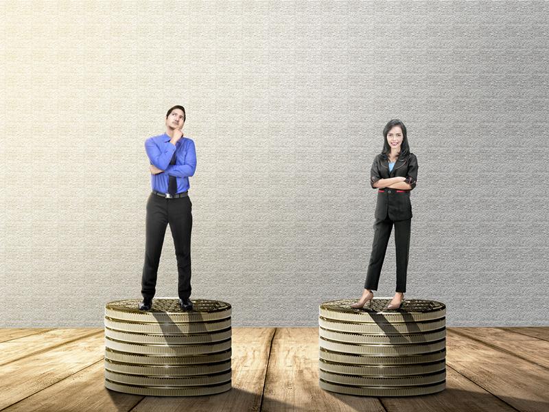 Un homme et une femme se tenant chacun sur une pile de pièces de monnaie.