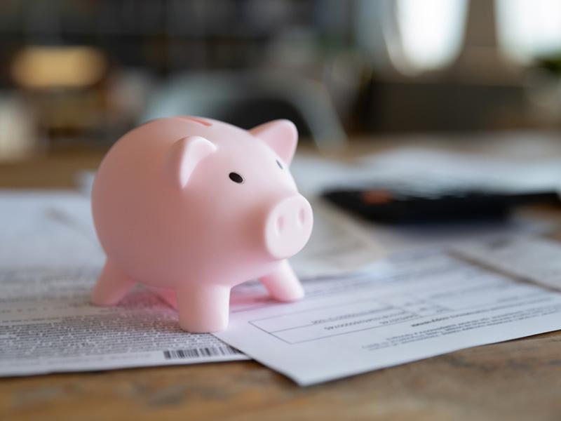 Tirelire en forme de cochon rose posée sur des documents ressemblant à des factures.