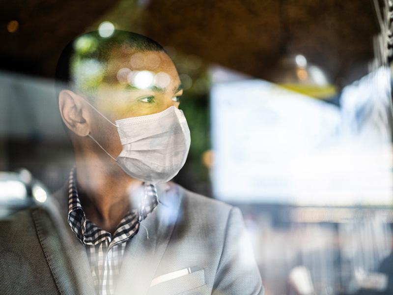 Un homme asiatique portant un masque, regarde au loin.