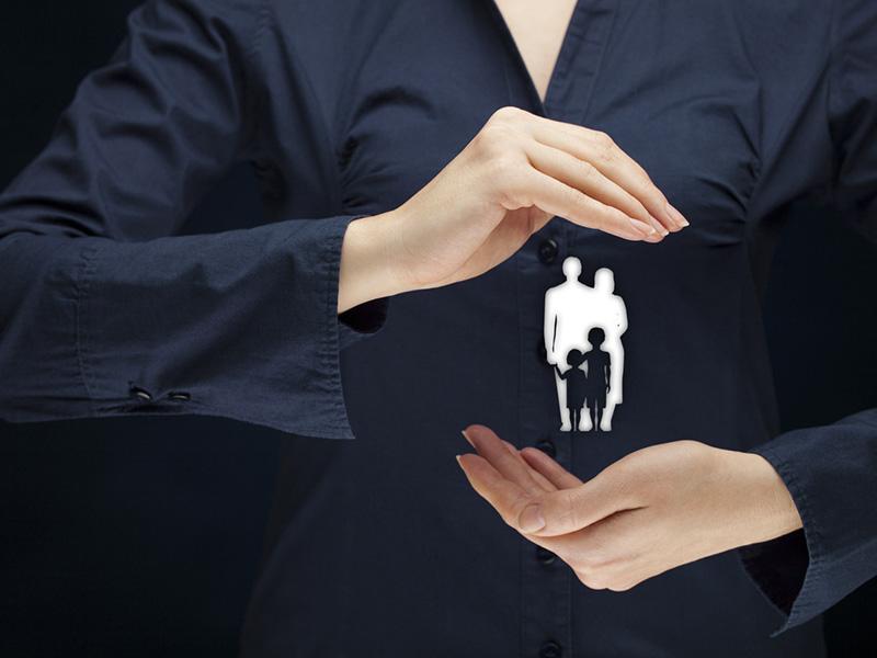 Femme entourant une famille miniature avec ses mains en guise de protection.