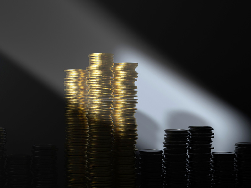 Piles de pièces d'or éclairées par un rayon de lumière.