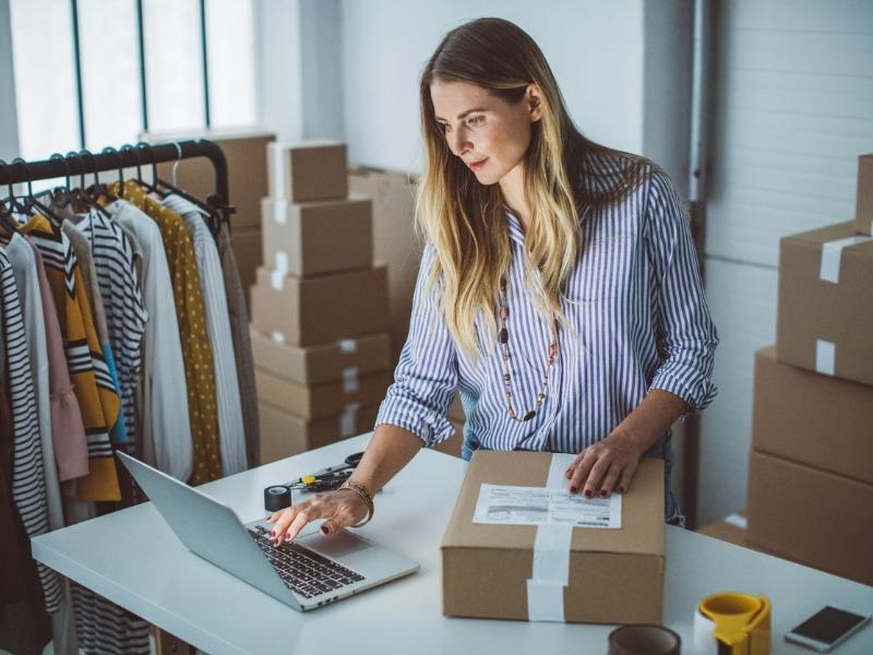 Une femme faisant des boîtes dans un magasin de vêtements.