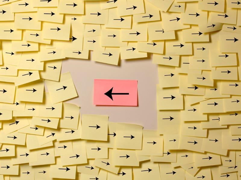 Un post it rose montrant la gauche au milieu d'une mer de post-it jaune montrant la droite.