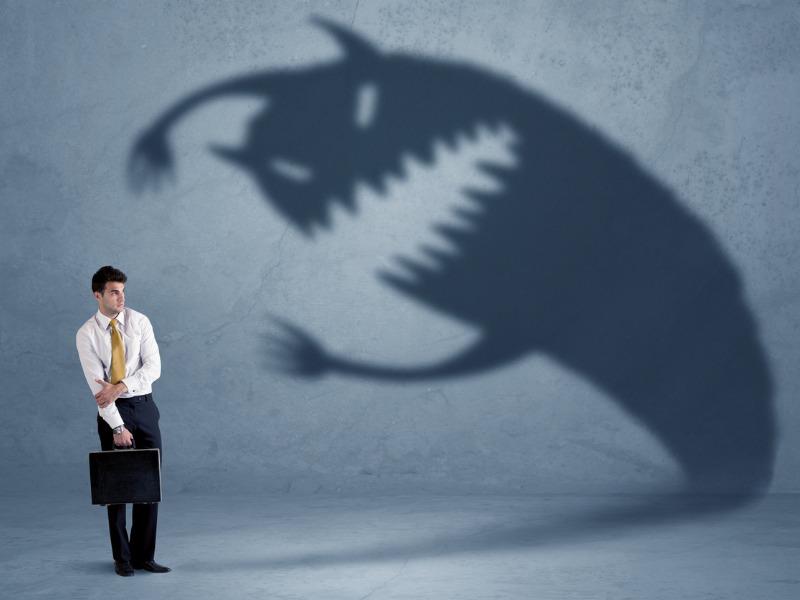 Un homme d'affaire qui craint une ombre pleine de dents.