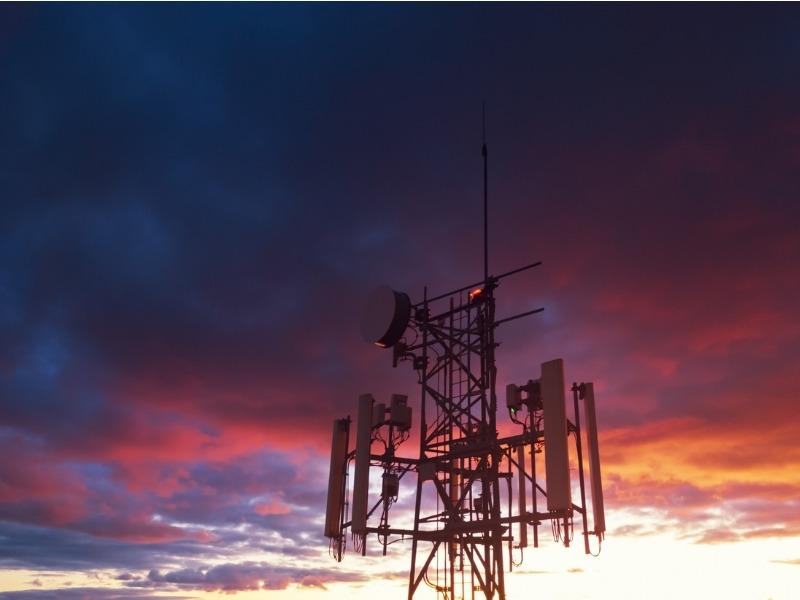 Une tour de télécommunication sur un fonds de ciel nuageux au coucher du soleil.