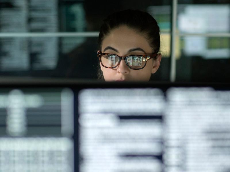Une femme analysant des données sur plusieurs écrans d'ordinateurs.