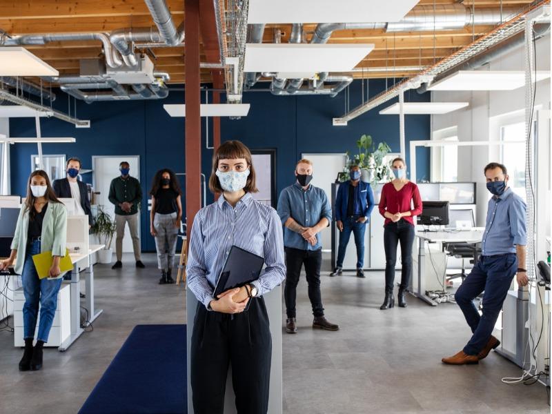 Plusieurs travailleurs masqués dans un bureau.