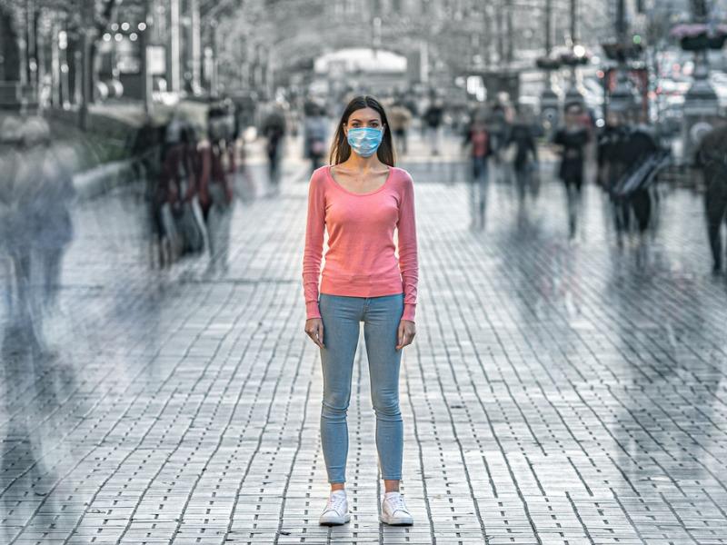 Une jeune femme au milieu d'une place portant un masque médical.
