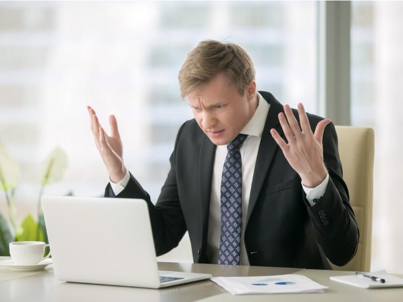 Un homme d'affaire qui regarde son écran et ne comprend pas.