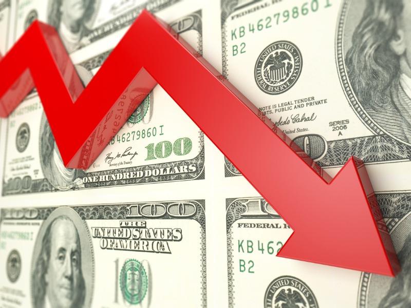 Une flèche rouge pointant vers le bas sur un fonds rempli de dollars américains.