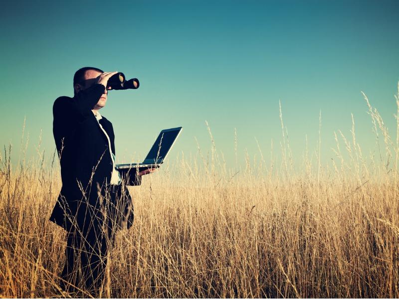 Un homme d'affaire au milieu d'un champ avec son ordinateur. Il regarde au loin avec des jumelles.