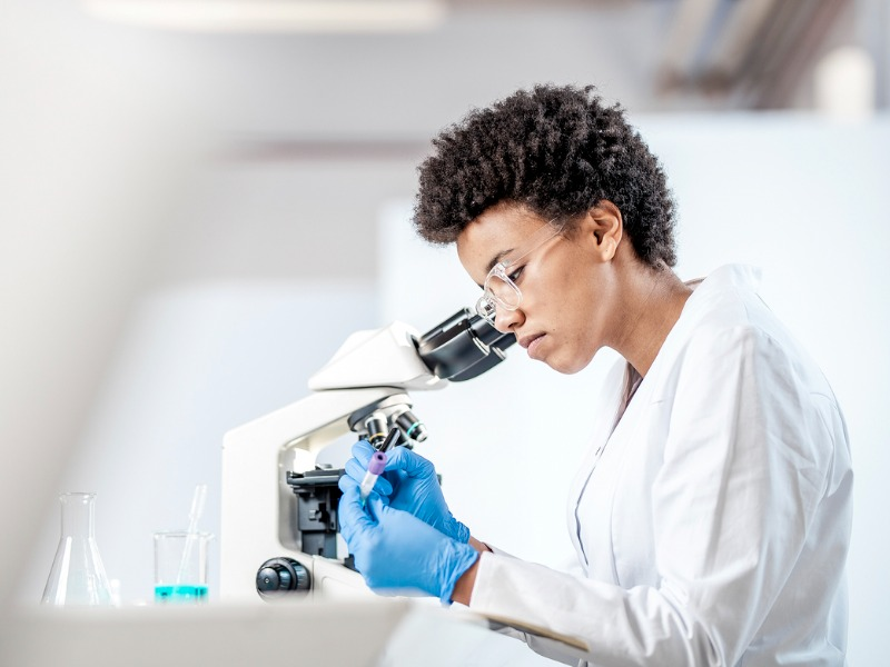 Une femme habillée en médecin étiquetant un tube à essai. Sur la table à côté d'elle on voit un microscope et des fioles.