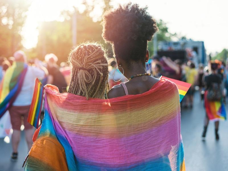 Deux jeunes femmes qui marchent en se tenant par la taille. Derrière elle, un drapeau de la Fierté.