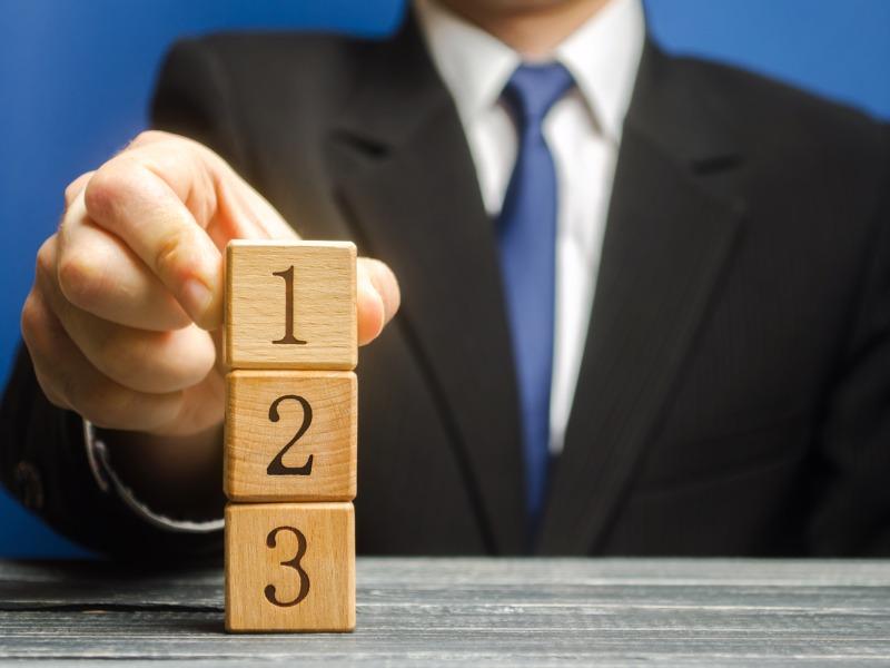 Un homme d'affaires posant un cube portant le numéro 1, sur une colonne de deux autres cubes portant le numéro 2 et 3.