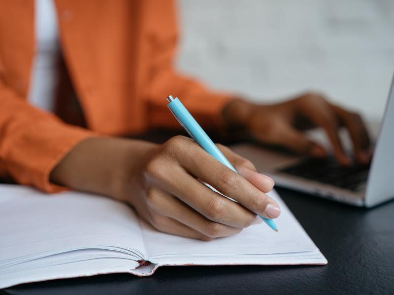 Une femme assise à une table devant son ordinateur. Elle écrit dans un cahier en regardant son écran.