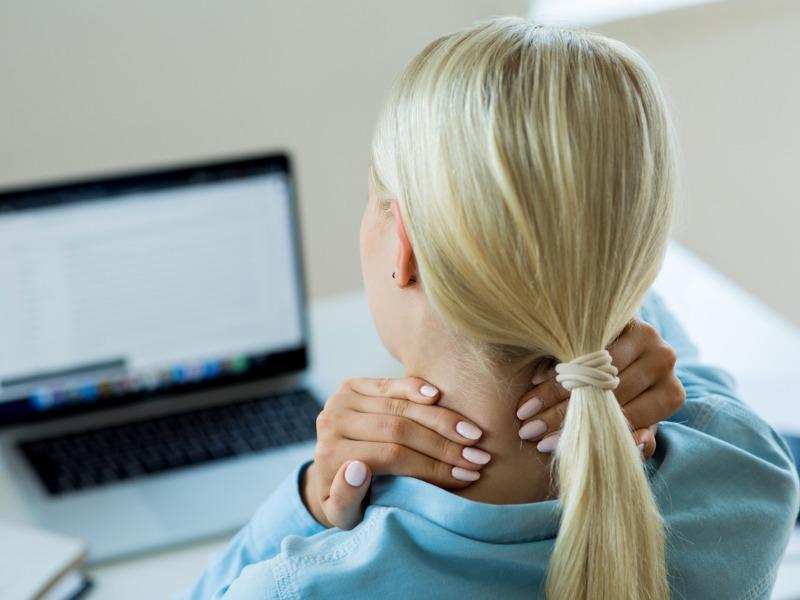Une femme assise devant un ordinateur sur un bureau. Elle se masse le cou.